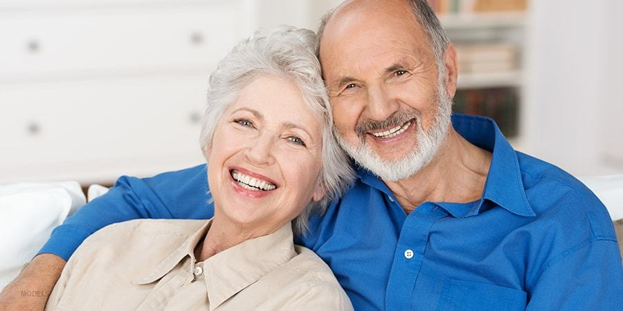 Elderly Couple Smiling and Holding Each Other on Couch