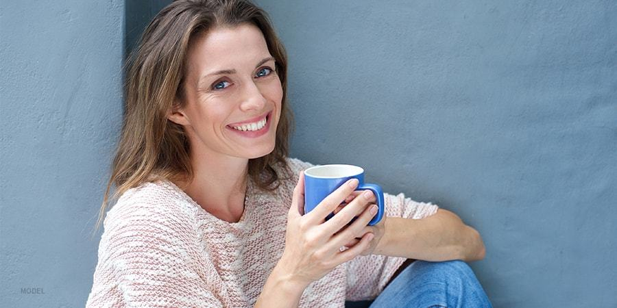Smiling Womam Sitting and Holding a Blue Mug