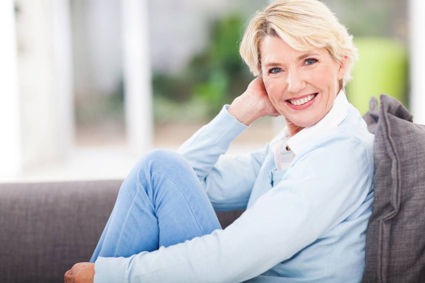 Blond Female Sitting On Gray Couch