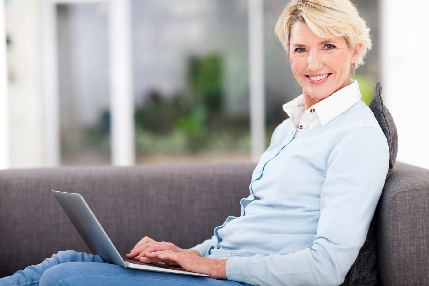 Blond Female Sitting On Couch With Laptop
