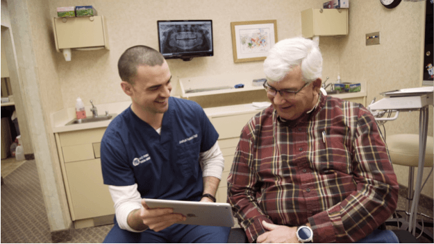 Mature Patient Looking at Tablet With Doctor