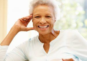 Elderly Woman Leaning On Couch with a Big Smile