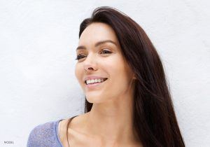 Woman with Long Brown Hair Gently Smiling and Looking Off